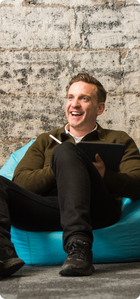 Young man sitting on blue beanbag, laughing whilst holding tablet