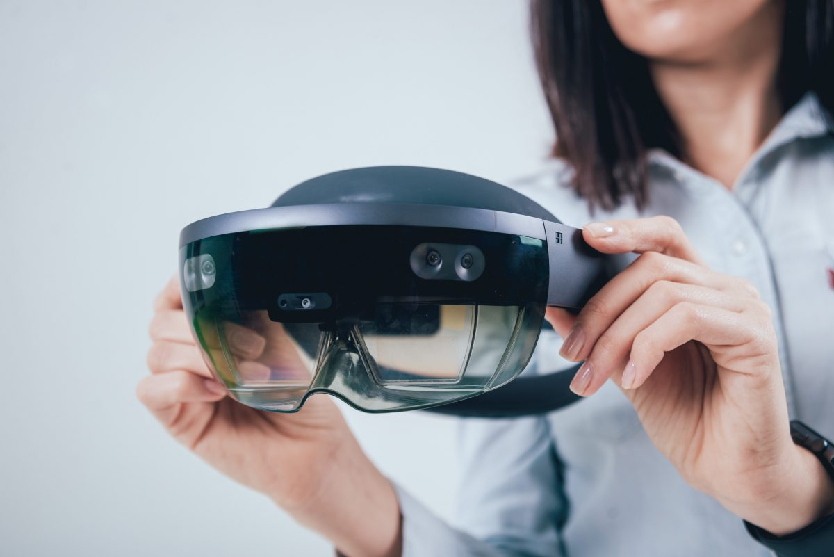 Women holding augmented or extended reality headset out in front of her.