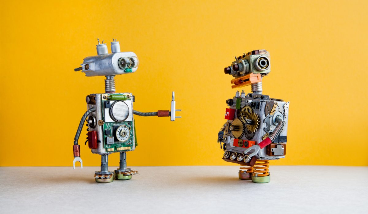 Two hand made robots discussing machine learning.