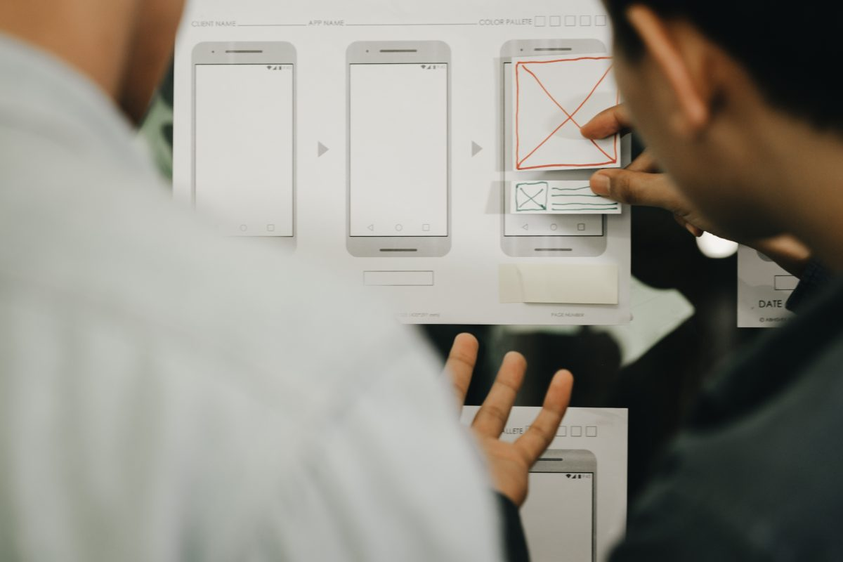 User interface designers working out sketched wireframe of app screens