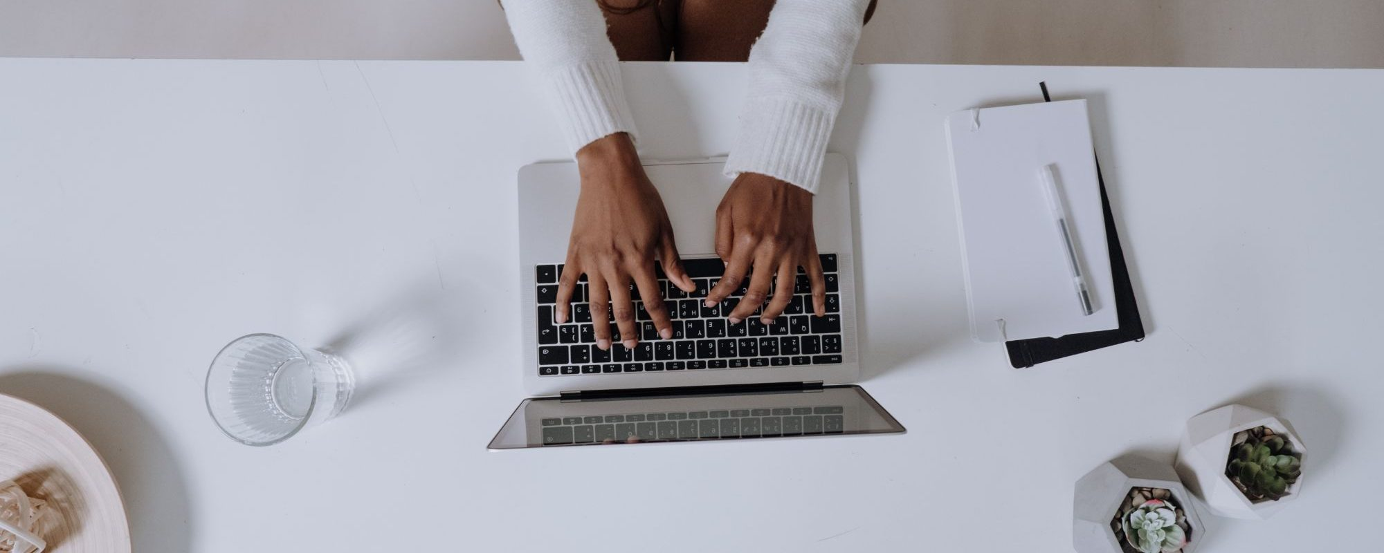 Remote worker at white desk typing on laptop
