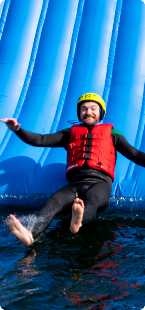 Smiling man on water slide. Company day out.