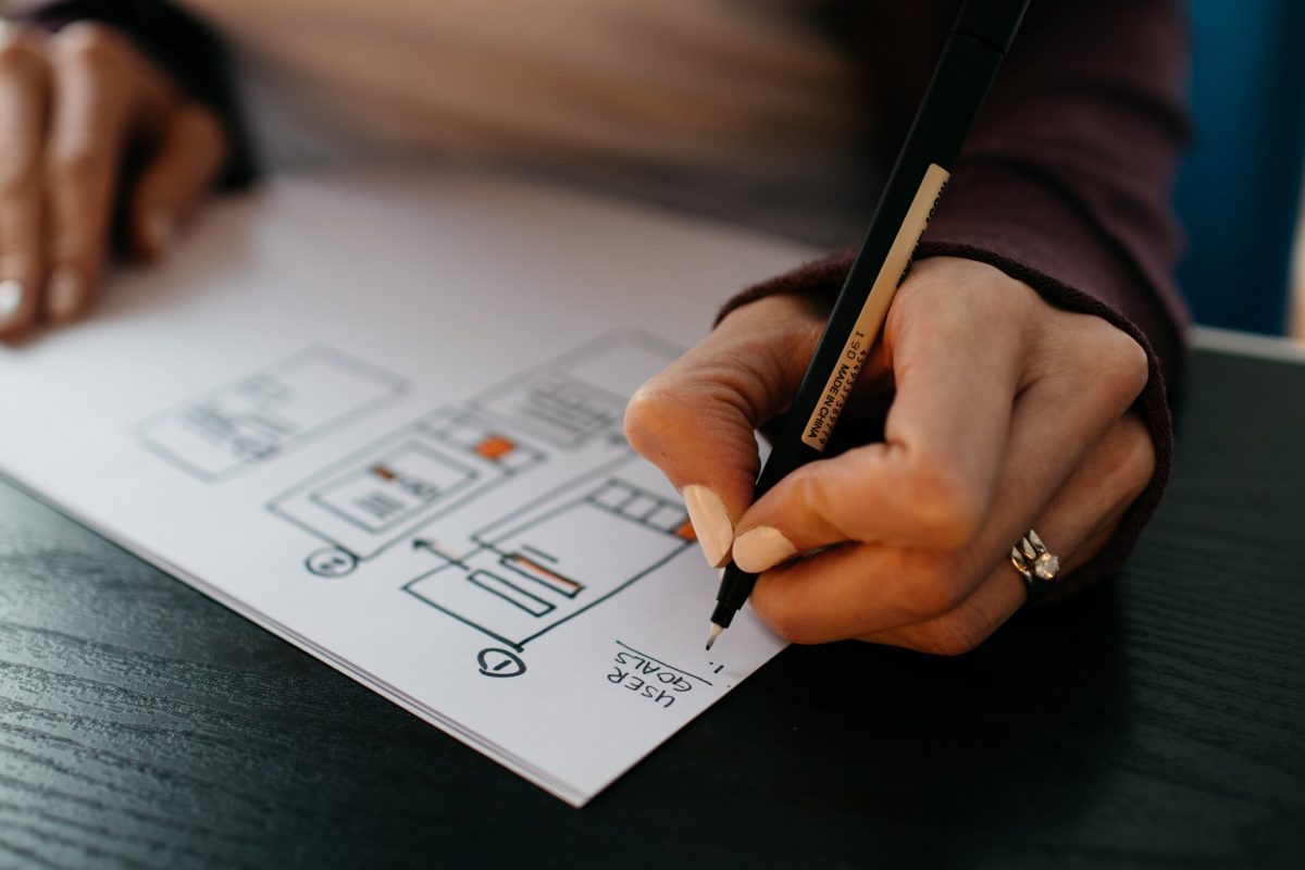 UX designer sketching out key user flows on paper with pen