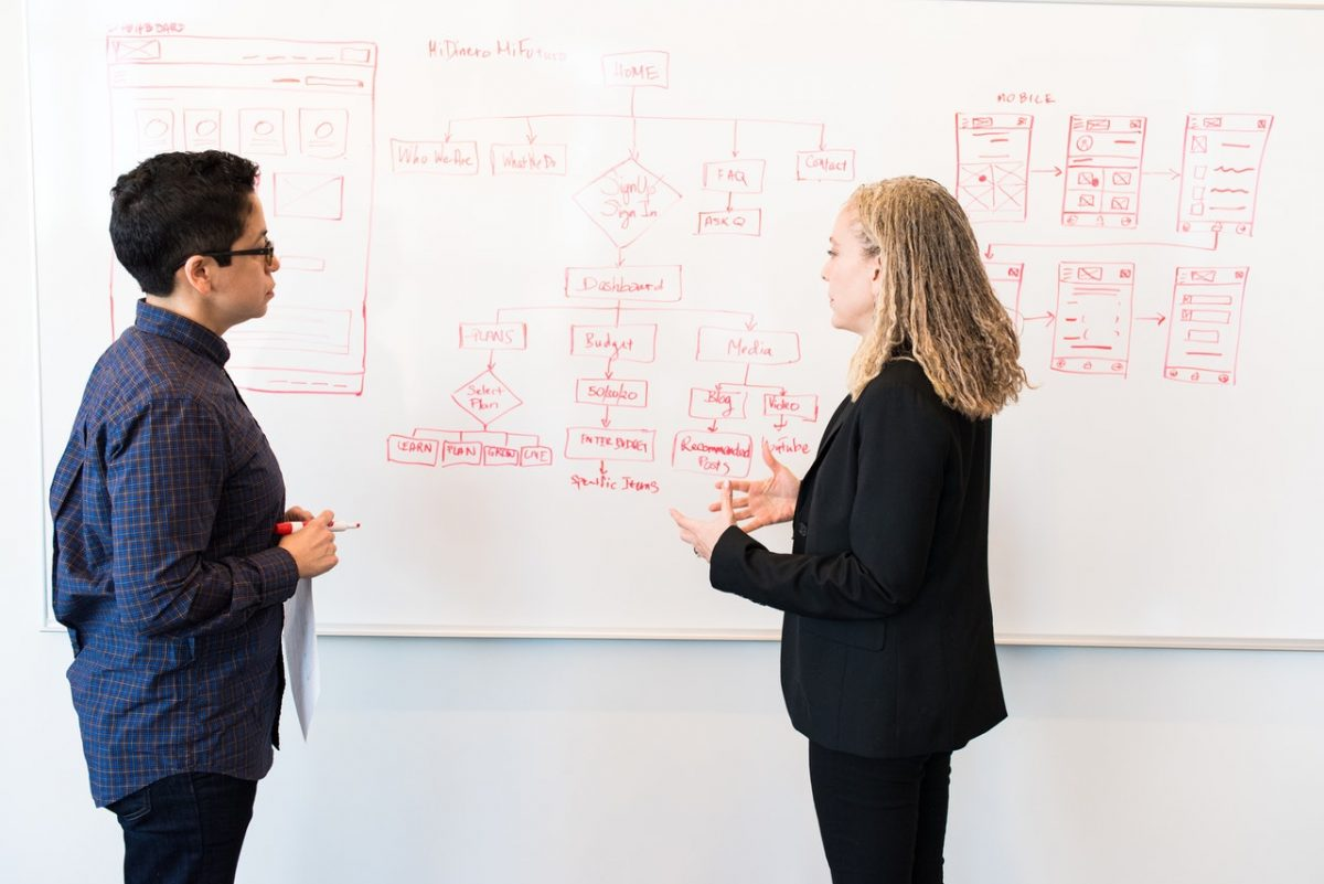 Two females discussing architecture and user flows for digital application